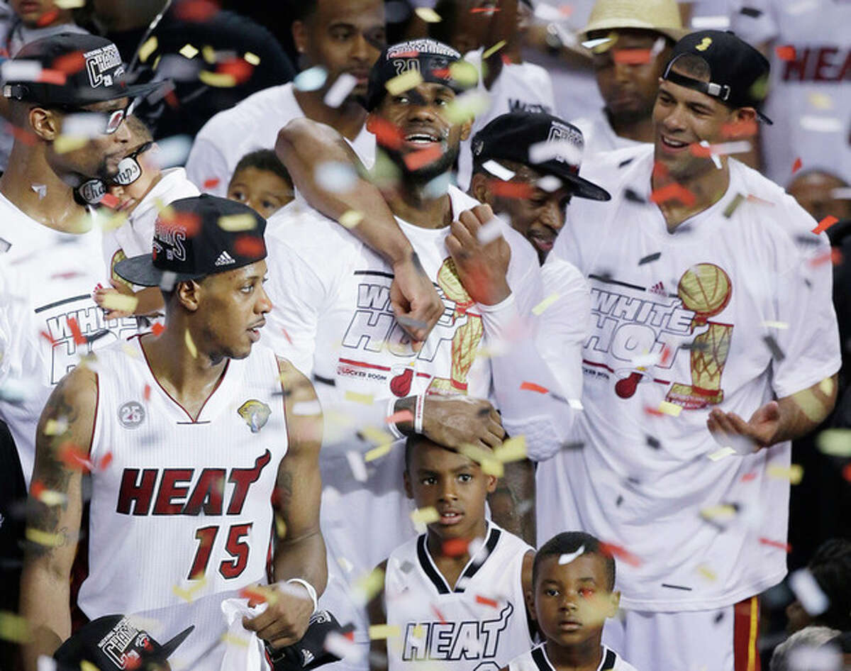 Miami Heat players including LeBron James, top center, celebrate after Game 7 of the NBA basketball championship game against the San Antonio Spurs, Friday, June 21, 2013, in Miami. The Miami Heat defeated the San Antonio Spurs 95-88 to win their second straight NBA championship. (AP Photo/Wilfredo Lee)