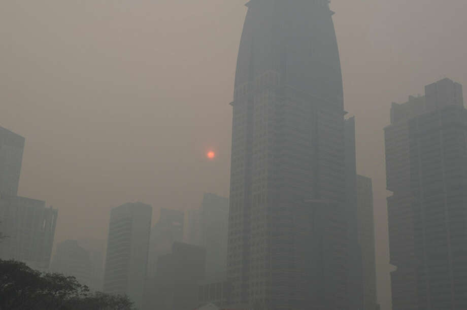 Singapore's central business district is obscured by haze Friday, June 21, 2013. Air pollution in Singapore has soared to record heights for a third consecutive day, as Indonesia prepared planes and helicopters to battle raging fires blamed for hazardous levels of smoky haze in three countries. (AP Photo/Joseph Nair) / AP
