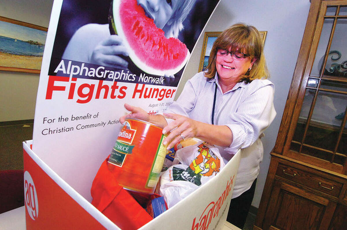 Hour photo / Alex von Kleydorff Norwalk City Clerk Erin Halsey grabs a 5-pound can of tomato sauce as she sorts through the AlphaGraphics Norwalk Fights Hunger donation box located at City hall. The food benefits Christian Community Action.
