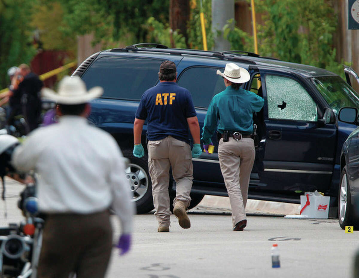 AP photo / Houston Chronicle, Mayra Beltran ATF and other investigators walk near a vehicle which was struck by a bullet near the scene where a gunman opened fire near the Texas A&M university on Monday in College Station, Texas.