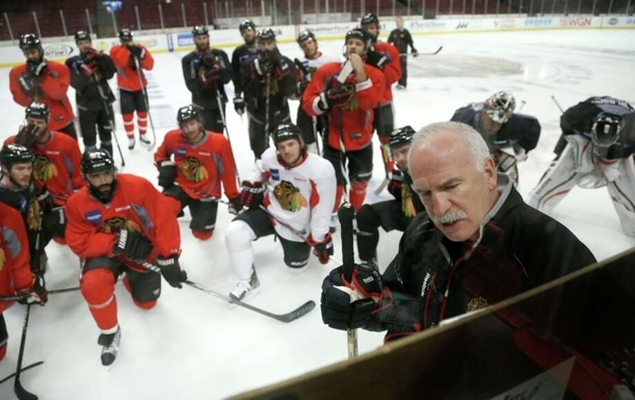 Chicago Blackhawks head coach Joel Quenneville, right, diagrams a drill during an NHL hockey practice Friday, June 21, 2013 in Chicago. The Blackhawks will host the Boston Bruins in Game 5 of the Stanley Cup Final series Saturday. (AP Photo/Charles Rex Arbogast) / AP