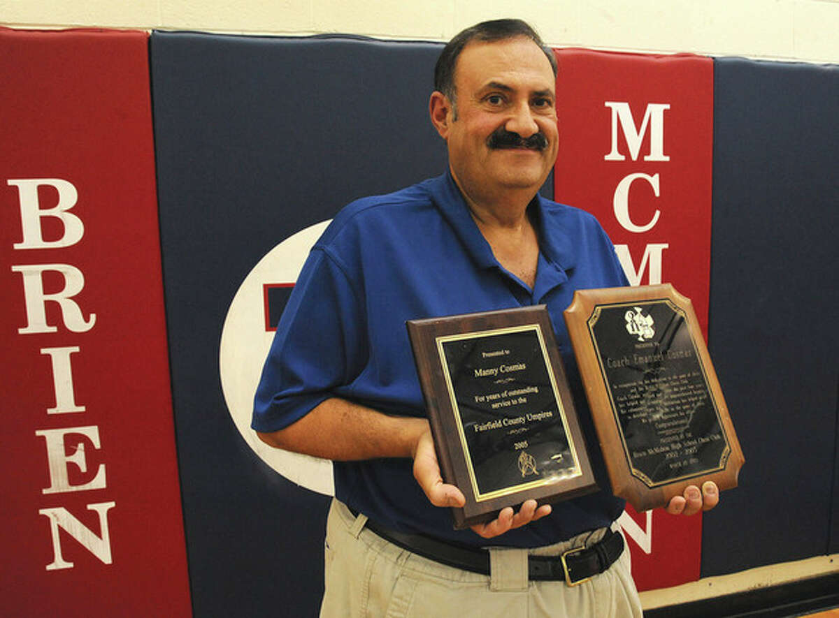 Hour photo / Matthew Vinci Brien McMahon teacher Manny Cosmas holds two plaques, one for the chess club and the other for FCIAC Umpire of the Year. Cosmas will retire this year.