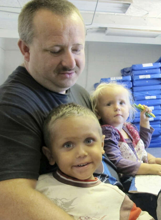 This June 20, 2013 image shows William Roper holding his 4-year-old son William Jr. and 2-year-old daughter Kacie during an interview at Joy Junction homeless shelter in Albuquerque, N.M. A report released by the Annie E. Casey Foundation shows the number of children living in poverty increased to 23 percent in 2011. The survey ranks New Mexico as the worst in the nation when it comes to child well-being. (AP Photo/Susan Montoya Bryan)