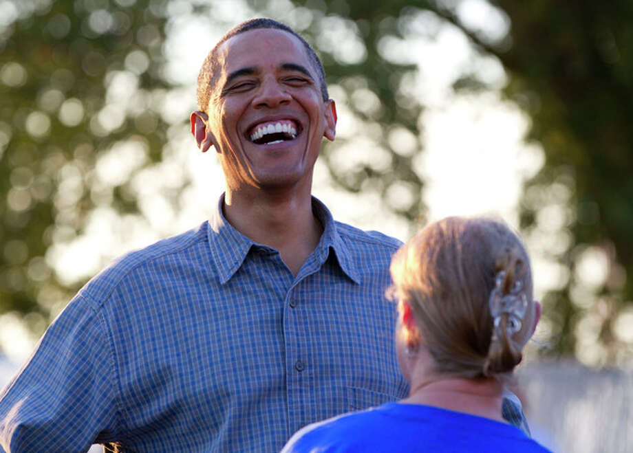 President Barack Obama laughs as he talks with people during a visit to the Iowa State Fair, Monday, Aug. 13, 2012, in Des Moines, Iowa. The president is on a three-day campaign bus tour through Iowa. (AP Photo/Carolyn Kaster) / AP