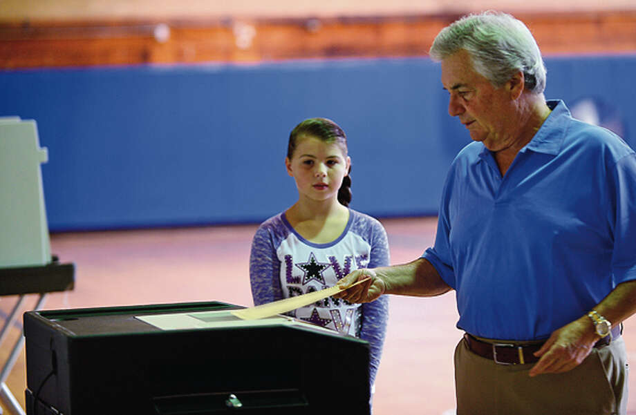 Norwalk resident Gary Oberst turns out to votes in the primary at Nathan Hale Middle School Tuesday while his grandaughter, Rachel Oberst, looks on. Hour photo / Erik Trautmann / (C)2012, The Hour Newspapers, all rights reserved