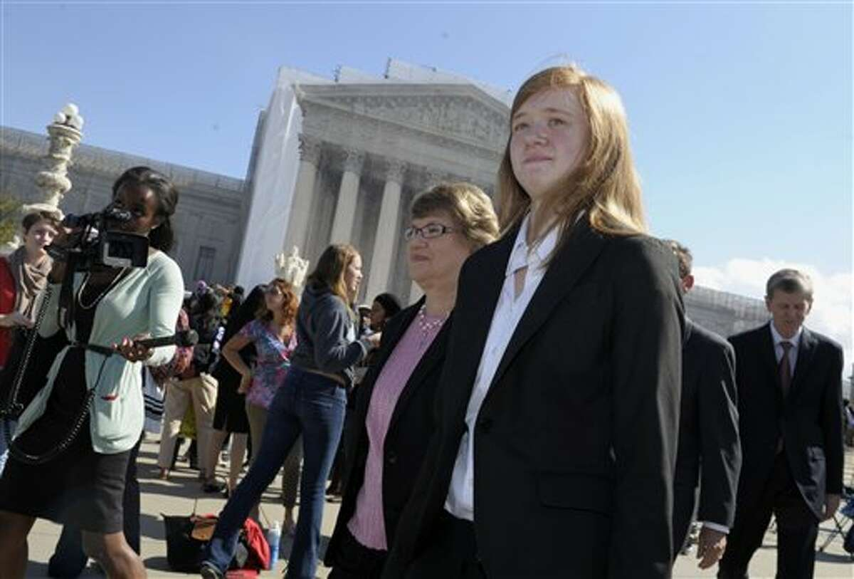 FILE - In this Oct. 10, 2012 file photo, Abigail Fisher, right, who sued the University of Texas, walks outside the Supreme Court in Washington. The Supreme Court has sent a Texas case on race-based college admissions back to a lower court for another look. The court's 7-1 decision Monday leaves unsettled many of the basic questions about the continued use of race as a factor in college admissions. (AP Photo/Susan Walsh, File)