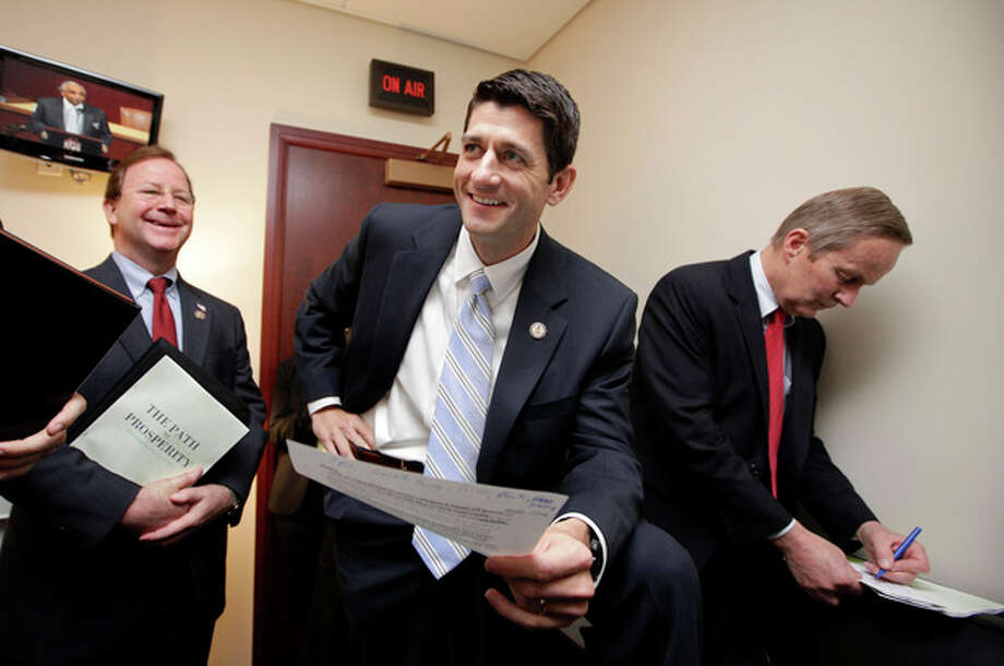 FILE - In this April 5, 2011 file photo, Republican Vice Presidential candidate, House Budget Committee Chairman Paul Ryan, R-Wis., works with Republican members of the committee on Capitol Hill in Washington before introducing his Path to Prosperity. At right is Rep. Todd Akin, R-Mo., with Rep. Bill Flores, R-Texas, at left. Paul Ryan traveled a perilous route to political stardom. While other lawmakers nervously whistled past trillion-dollar deficits, fearing to cut popular programs, he waded in with a machete and a smile. Ryan wants to slice away at Medicare, Social Security, food stamps and virtually every other government program but the military. (AP Photo/J. Scott Applewhite, File) / AP
