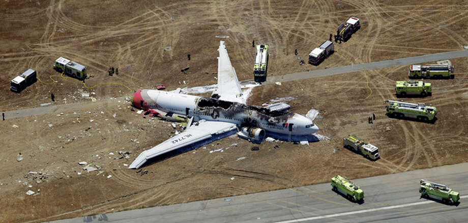 FILE - This July 6, 2013, file photo shows the wreckage of Asiana Flight 214 on the ground after it crashed at the San Francisco International Airport, in San Francisco. When the courts have to figure compensation for people aboard Flight 214, the potential payouts will probably be vastly different for Americans and passengers from other countries. A pact is likely to close U.S. courts to many foreigners and force them to pursue their claims in Asia and elsewhere, where lawsuits are rarer, harder to win (AP Photo/Marcio Jose Sanchez, File) / AP
