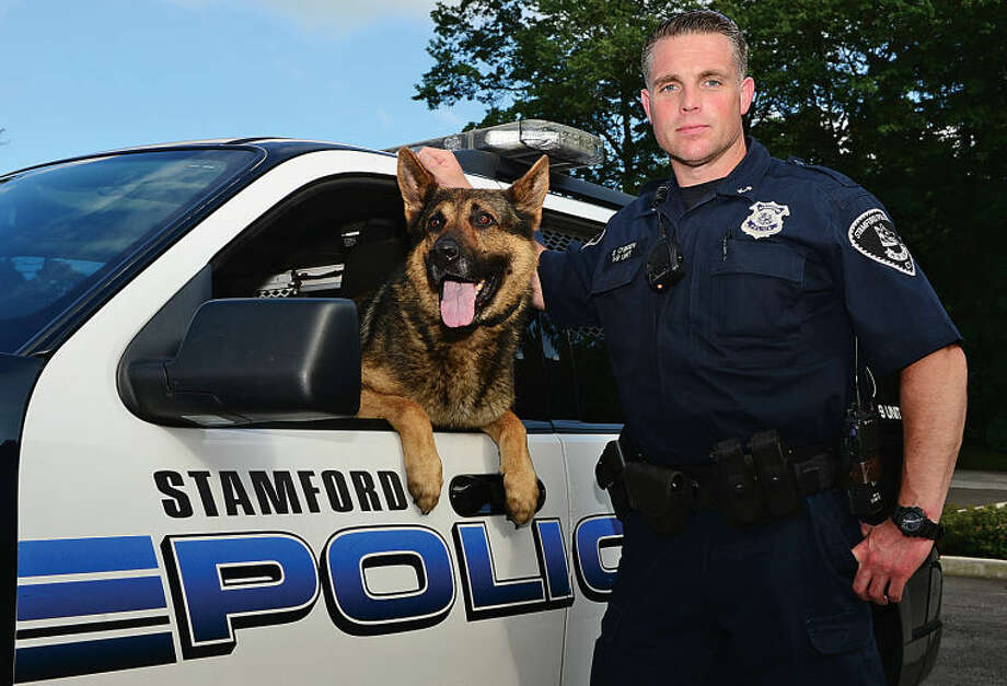 Stamford Officer of the Year Seth O'Brien stands alongside police service dog Cooper. O'Brien was instrumental in relaunching the department's K-9 unit several years ago.
