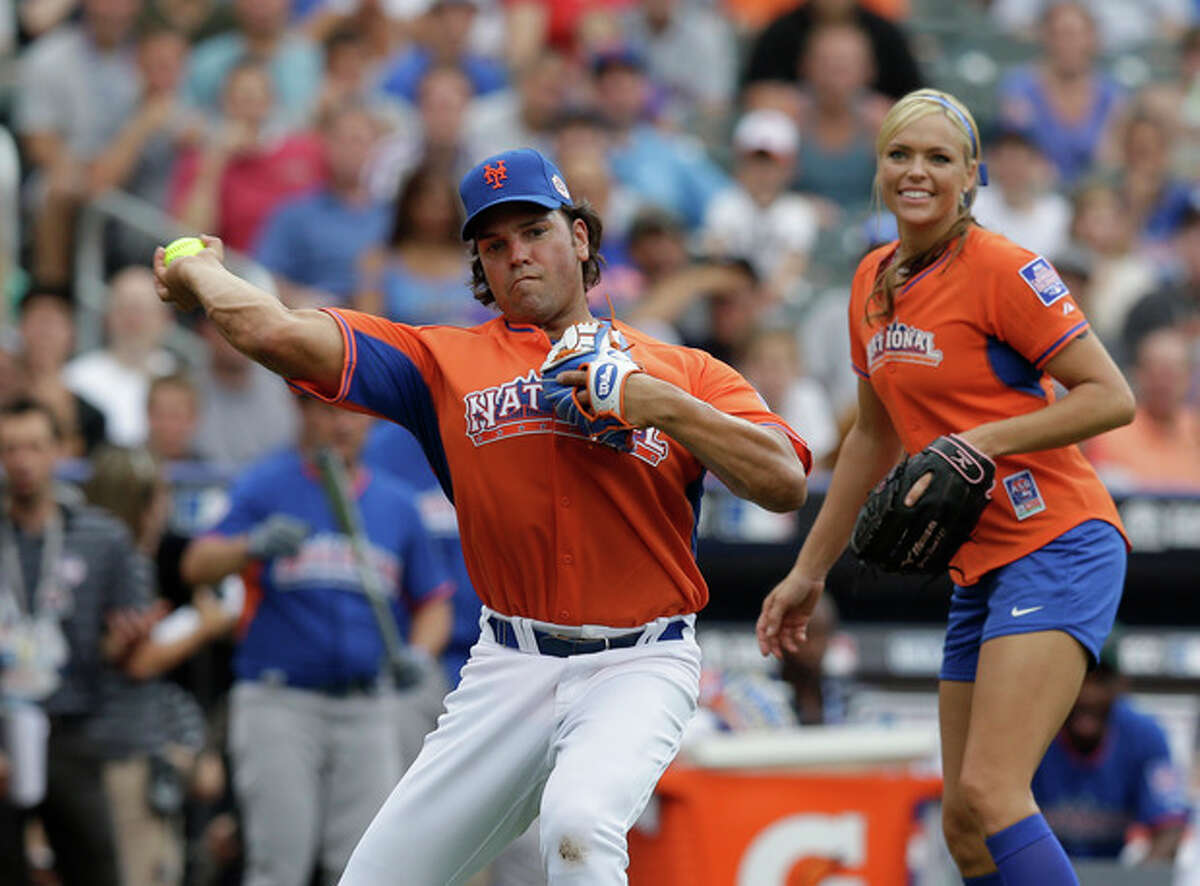 Former New York Mets catcher Mike Piazza makes a play during the All Star Legends & Celebrity Softball Game on Sunday, July 14, 2013 in New York. Former softball player Jennie Finch is at right. (AP Photo/Kathy Willens)