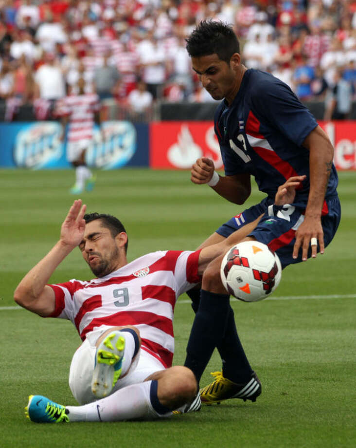 Cuba's Jorge Luis Corrales, right, and United States' Herculez Gomez (9) battle for a ball during the first half of a CONCACAF Gold Cup soccer game on Saturday, July 13, 2013, in Sandy, Utah. (AP Photo/Rick Bowmer)