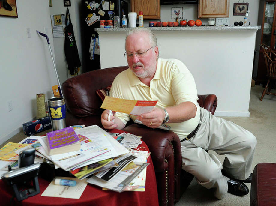 Greg Mann, an unemployed research analyst and real estate appraiser, sorts and cuts coupons at his home Tuesday, Aug. 14, 2012, in Braselton, Ga.. The recession that ended three years ago lingers on as the worst economic recovery since the Great Depression. (AP Photo/John Amis) / FR69715 AP
