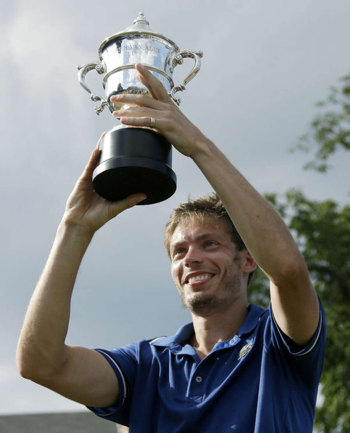 Nicolas Mahut, of France, hoists the Van Alen Cup after defeating Lleyton Hewitt, of Australia, in the finals of the Hall of Fame Tennis Championships in Newport, R.I. Sunday, July 14, 2013. Mahut won 5-7, 7-5, 6-3. (AP Photo/Elise Amendola)