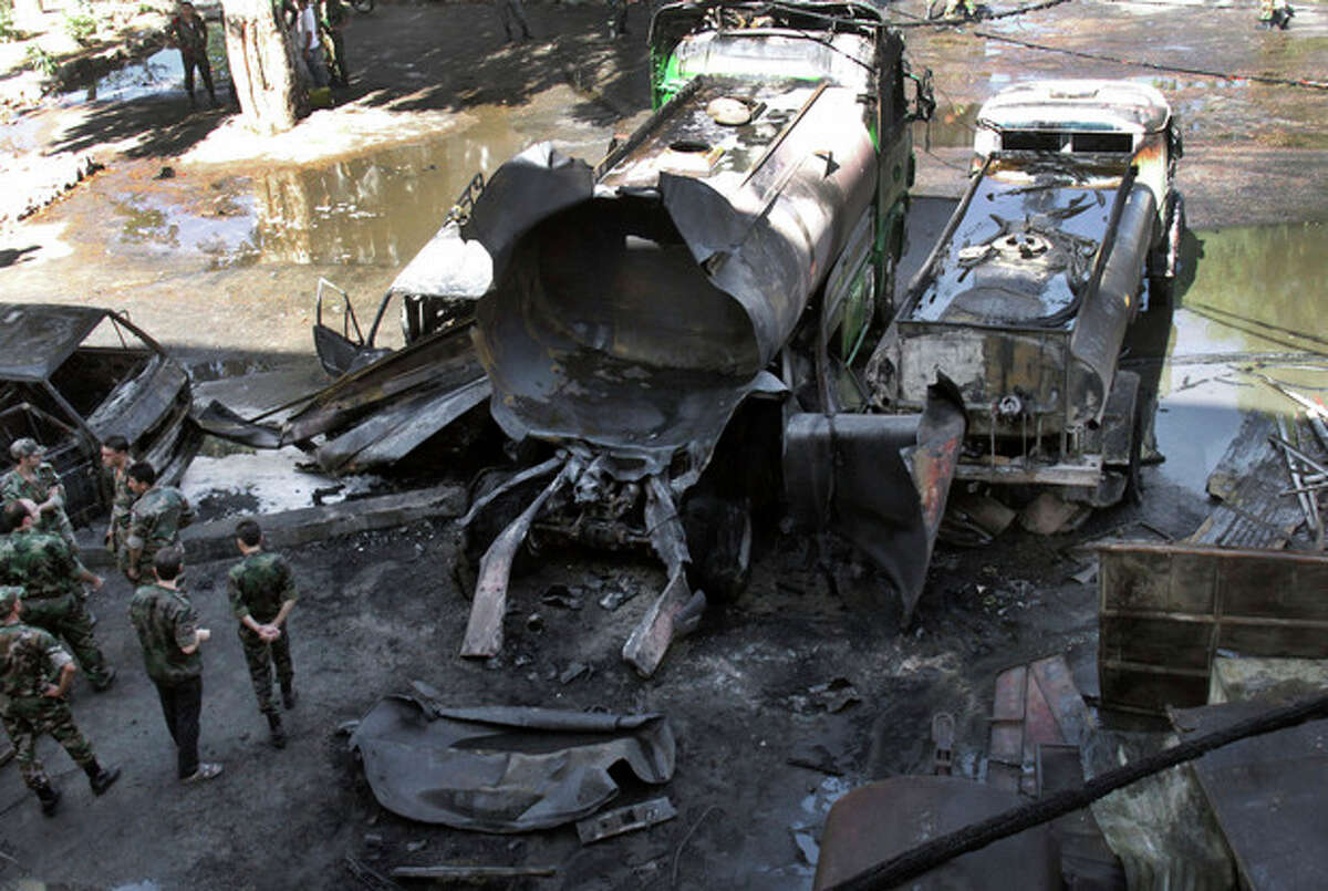 Syrian soldiers investigate the scene after a bomb attached to a fuel truck exploded outside a Damascus hotel where U.N. observers are staying in Damascus, Syria, Wednesday, Aug. 15, 2012. Several people were wounded, Syria's state TV reported. TV said the explosion took place near a parking lot used by the army command, which is about 300 meters (yards) away. (AP Photo/Bassem Tellawi)