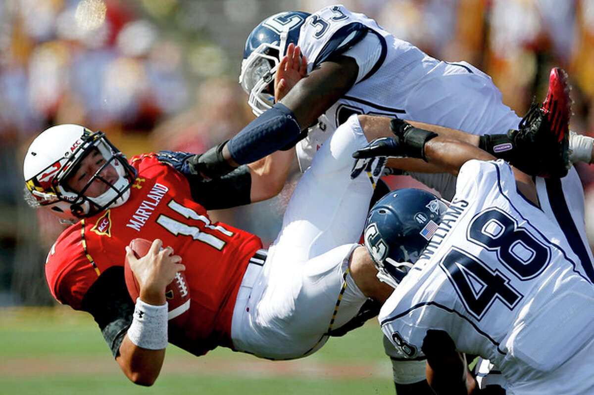 Maryland quarterback Perry Hills (11) is tackled by Connecticut's Yawin Smallwood, top right, and Trevardo Williams in the second half of an NCAA college football game in College Park, Md., Saturday, Sept. 15, 2012. Connecticut won 24-21. (AP Photo/Patrick Semansky)