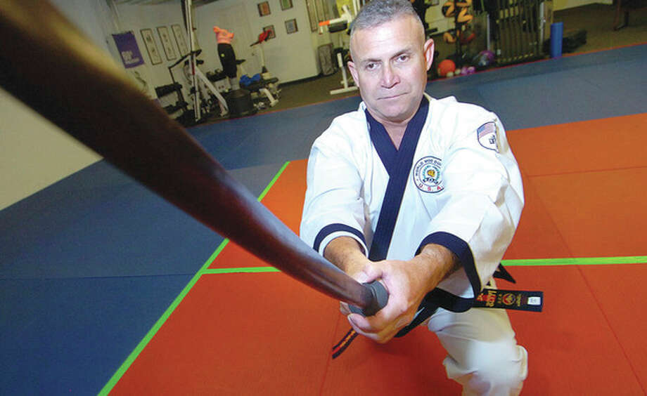 Hour Photo/ Alex von Kleydorff. U.S. Soo Bahk Do Master Chief instructor and hall of famer Robert Z Olmedo uses a wooden training sword in his Wilton studio / 2012 The Hour Newspapers