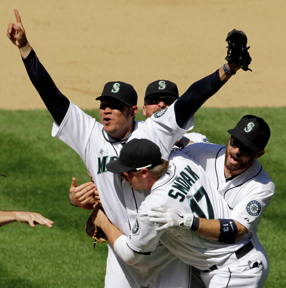 Seattle Mariners pitcher Felix Hernandez celebrates with teammates, including Justin Smoak (17), after throwing a perfect game in the Mariners' 1-0 win over the Tampa Bay Rays in a baseball game, Wednesday, Aug. 15, 2012, in Seattle. (AP Photo/The Seattle Times, Mark Harrison) MAGS OUT; NO SALES; SEATTLEPI.COM OUT; MANDATORY CREDIT; USA TODAY OUT; TV OUT / The Seattle Times