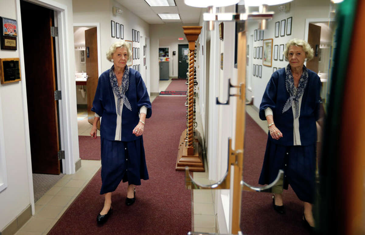 In this Friday, July 12, 2013 photo, June Springer walks between offices where she works at Caffi Contracting Services, in Alexandria, Va. Springer who just turned 90, works as a receptionist. People who delay retirement have less risk of developing Alzheimer's disease or other types of dementia, a study of half a million people in France found. (AP Photo/Alex Brandon)