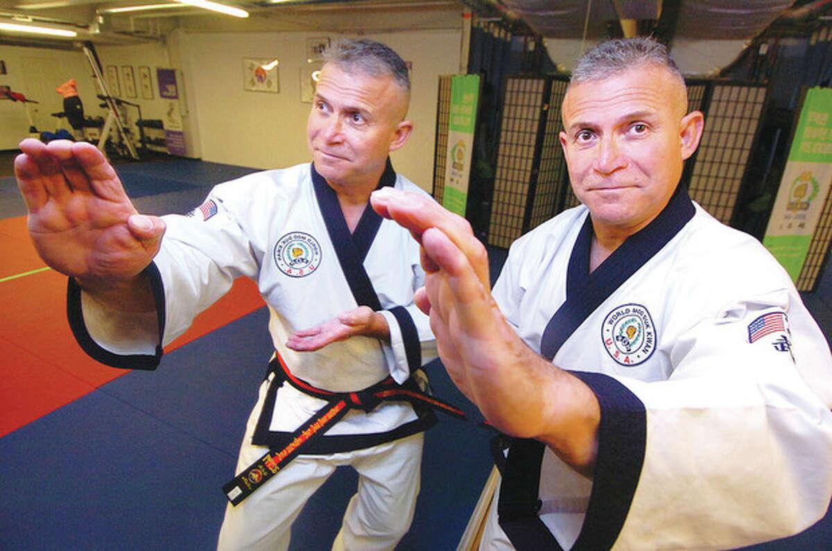 Photo by Alex von Kleydorff Robert Olmedo, who recently received a lifetime achievement award from the U.S. Martial Arts Hall of Fame, strikes a defensive stance in his Wilton karate studio, Olmedo Soo Bahk Do Karate.