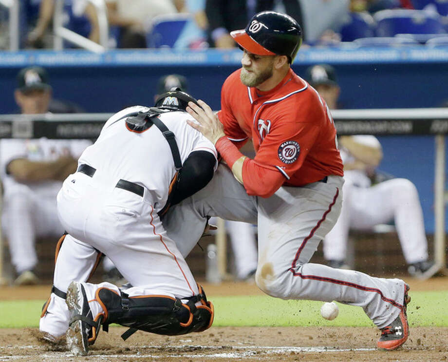 Washington Nationals' Bryce Harper, right, collides with Miami Marlins catcher Jeff Mathis at home plate to score during the fourth inning of a baseball game, Saturday, July 13, 2013 in Miami. Harper scored on a sacrifice fly by Jayson Werth. (AP Photo/Wilfredo Lee) / AP