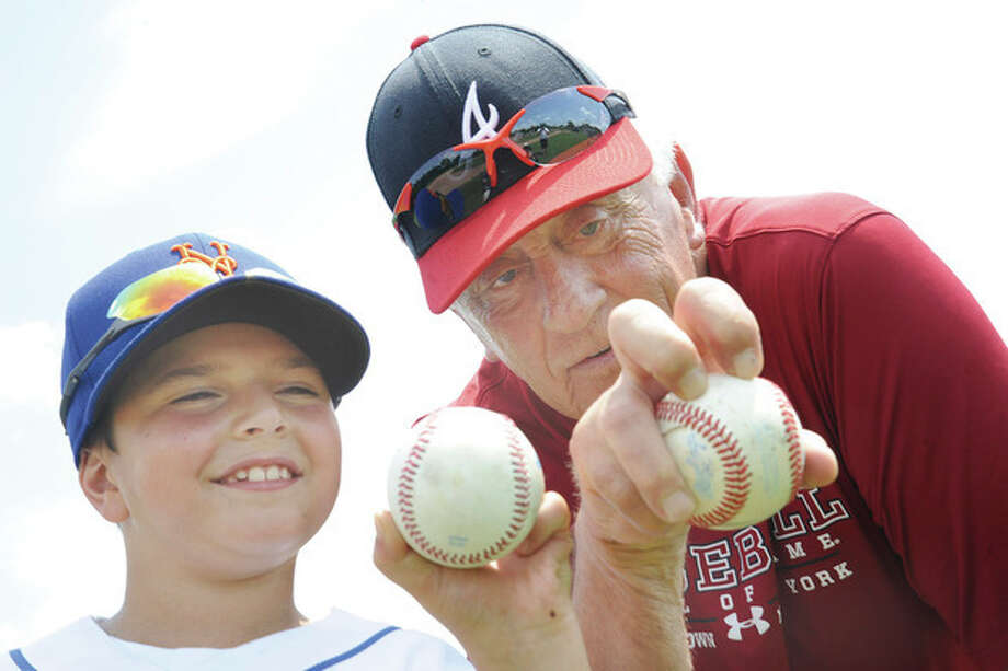 Hour photo/Matthew VinciBaseball Hall of Fame pitcher Phil Niekro, right, shows 8-year-old Trevor Diaco how to grip a knuckleball during Monday's Baseball World Training School session at Wakeman Field in Westport. Neikro was the guest instructor for Monday's gathering.