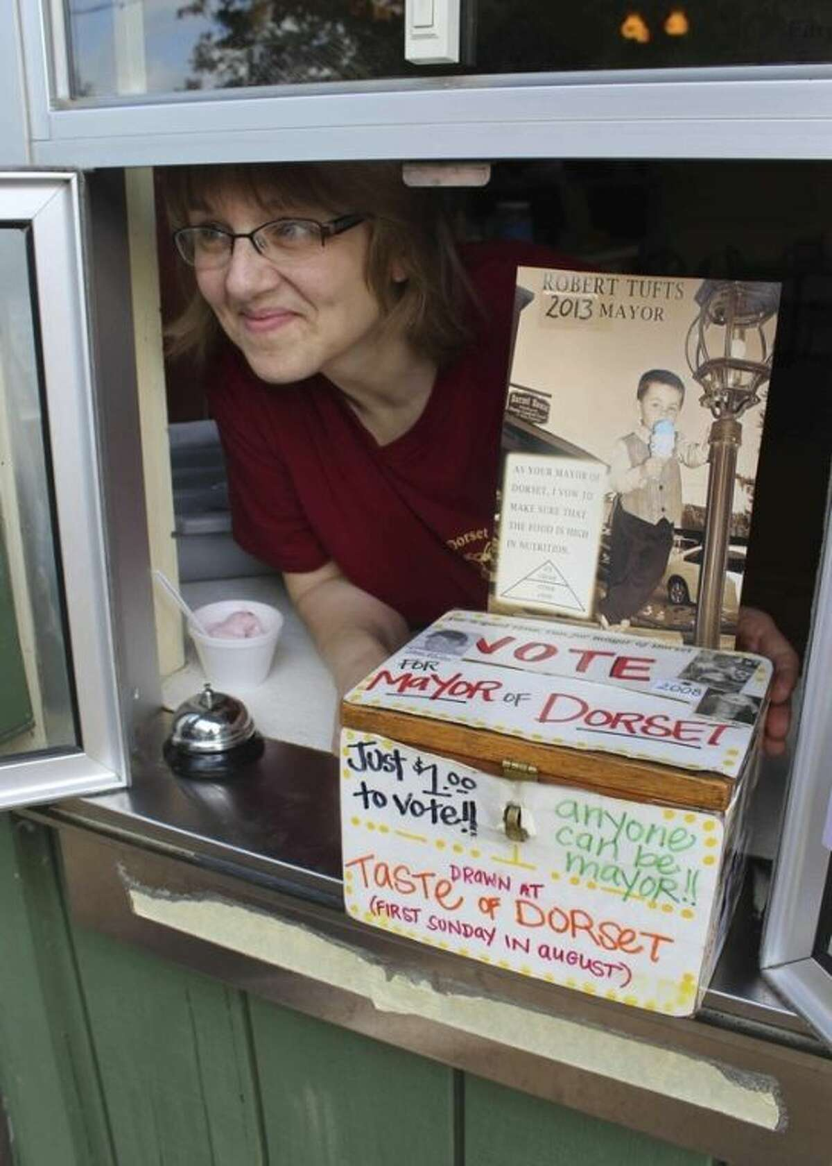 In this photo made Wednesday, June 26, 2013 in Dorset , Minn., Jeannette Dudley, co-owner of Dorset House Family Restaurant, poses by the ballot box at the window of her restaurant in the Dorset mayor race. Bobby Tufts, the 4-year-old mayor, is running for re-election. Bobby was only 3 when he won election last year as mayor of Dorset (population 22 to 28, depending on whether the minister and his family are in town). Dorset, which bills itself as the Restaurant Capital of the World, has no formal city government. (AP Photo/Jeff Baenen)