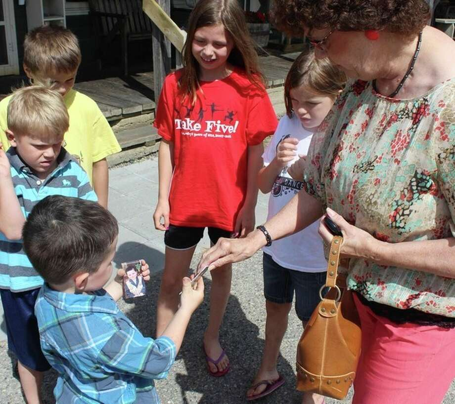 In this photo made Wednesday, June 26, 2013 in Dorset , Minn., Bobby Tufts, the 4-year-old mayor, hands out his card to potential voters for his re-election bid. Bobby was only 3 when he won election last year as mayor of Dorset (population 22 to 28, depending on whether the minister and his family are in town). Dorset, which bills itself as the Restaurant Capital of the World, has no formal city government. (AP Photo/Jeff Baenen) / AP