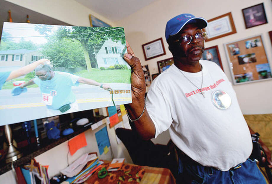 Hour photo / Erik TrautmannWilliam Adams, above and below, has walked numerous races around the area since 2000 with a cane. Below left, Adam's inspiration is his late daughter La'Tasha Vines, who died in Iraq. / (C)2012, The Hour Newspapers, all rights reserved