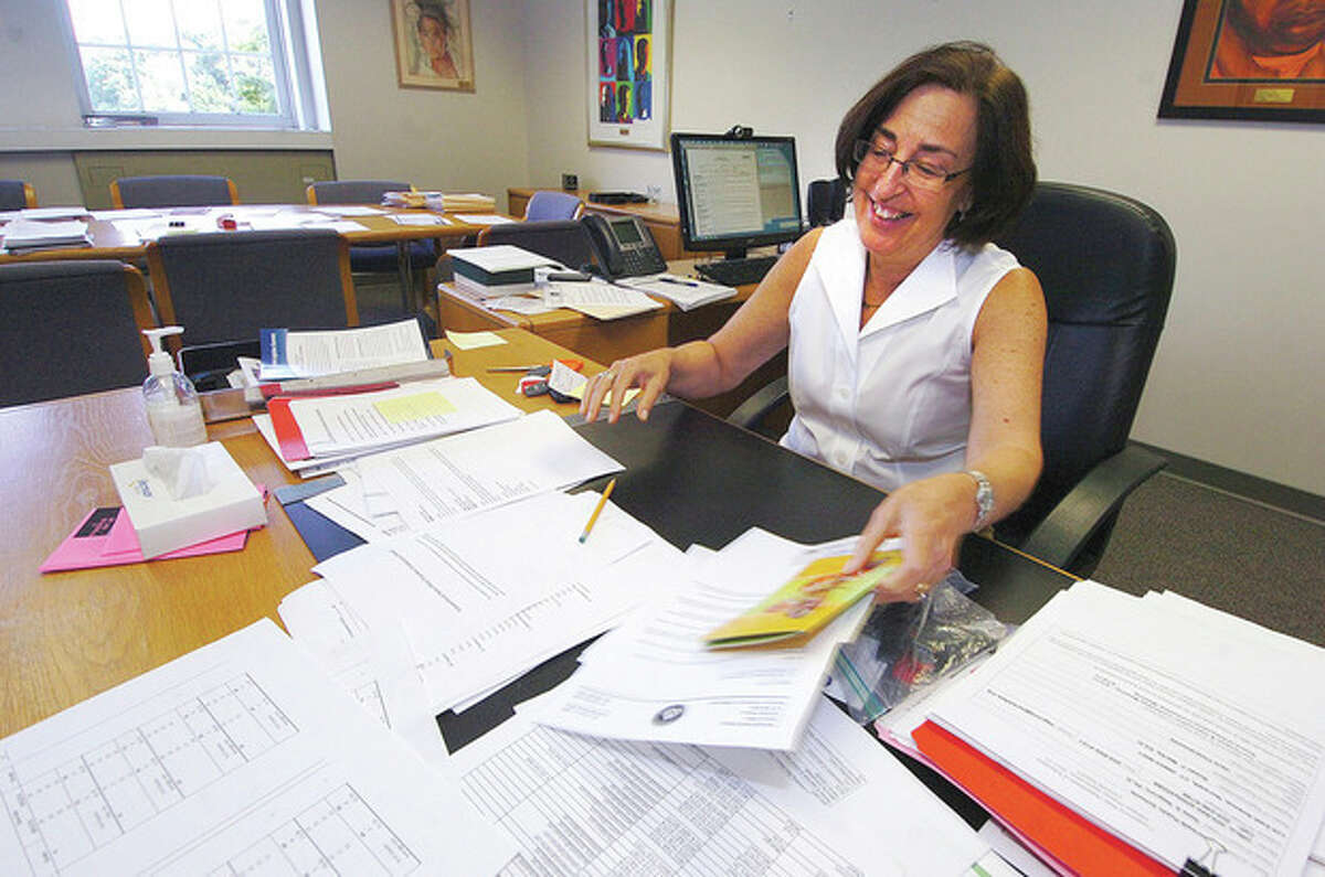Hour Photo/ Alex von Kleydorff. Dr. Susan marks organizes some of her paperwork as she packs her office on her last day as Superintedent of Norwalk schools.