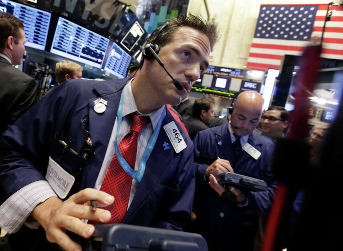 Trader Gregory Rowe, left, works on the floor of the New York Stock Exchange Monday, July 8, 2013. Stocks rose in early trading Monday ahead of the start of second-quarter corporate earnings reports. (AP Photo/Richard Drew)