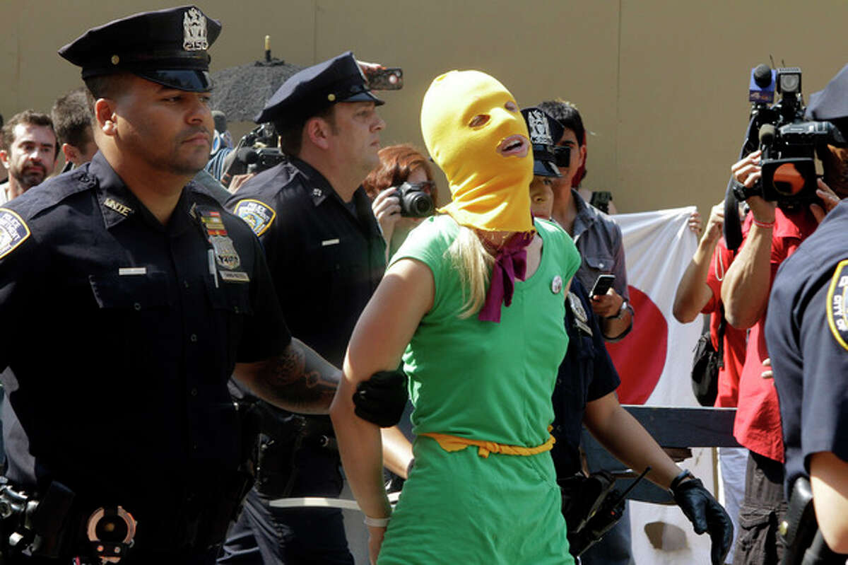 A protester is arrested during a demonstration in front of the Russian consulate in support of Russian punk band Pussy Riot, Friday, Aug. 17, 2012 in New York. A Russian judge found three members of the provocative punk band guilty of hooliganism on Friday, in one of the most closely watched cases in recent Russian history. The judge said the three band members committed hooliganism driven by religious hatred and offending religious believers. The three were arrested in March after a guerrilla performance in Moscow's main cathedral calling for the Virgin Mary to protect Russia against Vladimir Putin, who was elected to a new term as Russia's president a few days later. (AP Photo/Alex Katz)