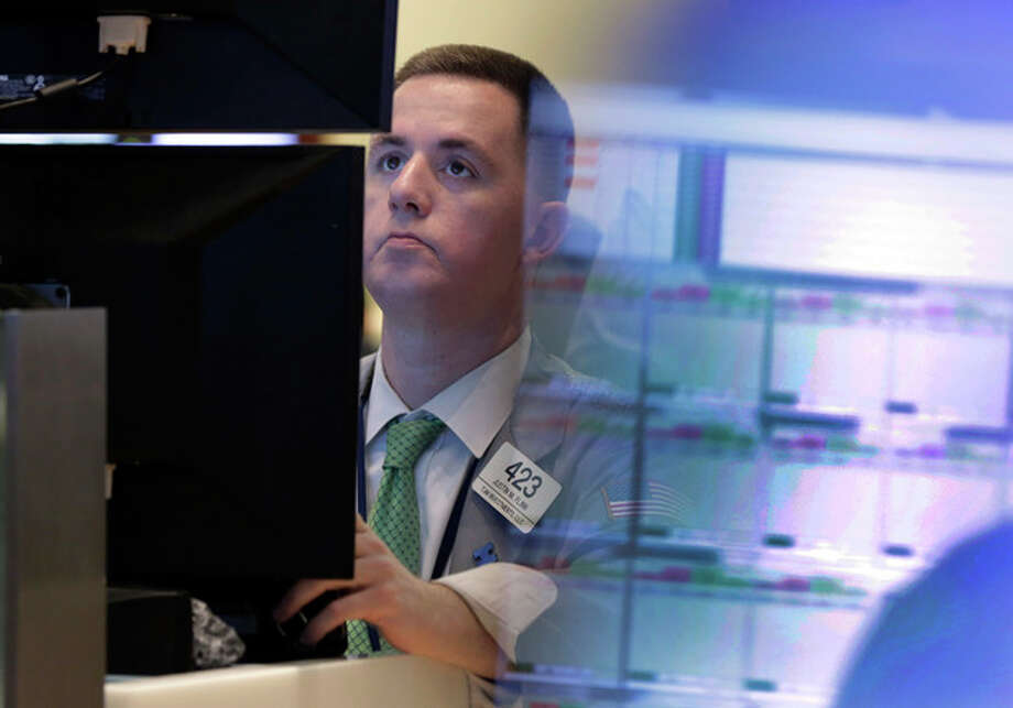 Trader Justin Flinn works in a booth on the floor of the New York Stock Exchange Monday, July 8, 2013. Stocks rose in early trading Monday ahead of the start of second-quarter corporate earnings reports. (AP Photo/Richard Drew) / AP