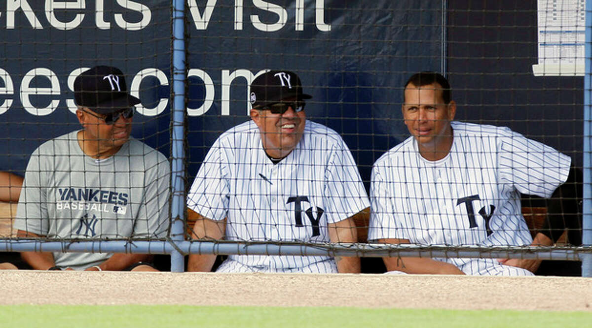 New York Yankees Alex Rodriquez, right, sits on the bench with Reggie Jackson, left and Tampa Yankees manager Luis Sojo, during a Tampa Yankees minor league baseball game against the Dunedin Blue Jays in Tampa, Fla., Wednesday, July 10, 2013. (AP Photo/Scott Iskowitz)