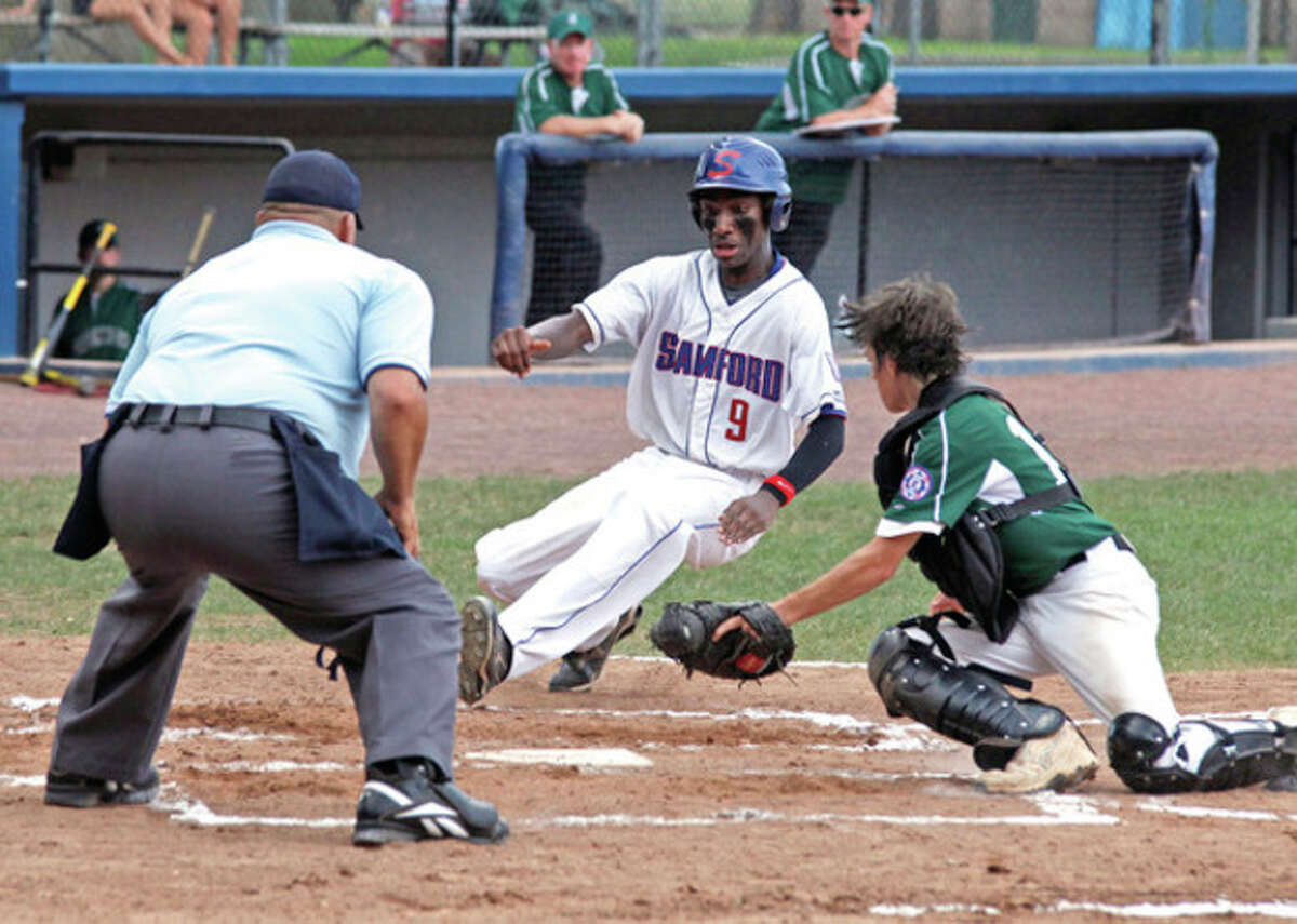 Photo by Danielle Calloway Stamford's Dave Lauture, center, slides into home during the Babe Ruth District 1 Championship game against Greenwich at Cubeta Field on Monday afternoon in Stamford. Stamford won, 3-2.