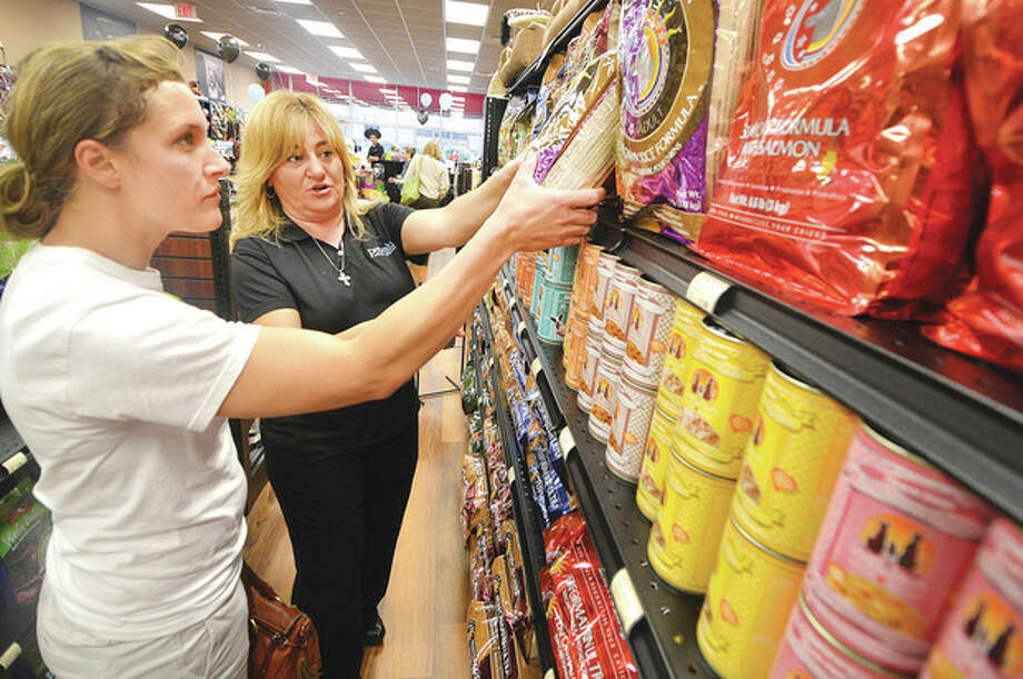 Hour Photo/Alex von Kleydorff Store Manager Stacey Christofrides helps custome Leigh Marsan with some natural dog food at Pet Valu during an opening reception at their new Norwalk location