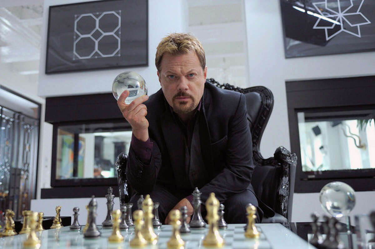 This undated publicity photo released by Muse/IFC shows Eddie Izzard, as crime lord Tannhauser, playing a little game of chess with someone known as God in IFC's new action comedy
