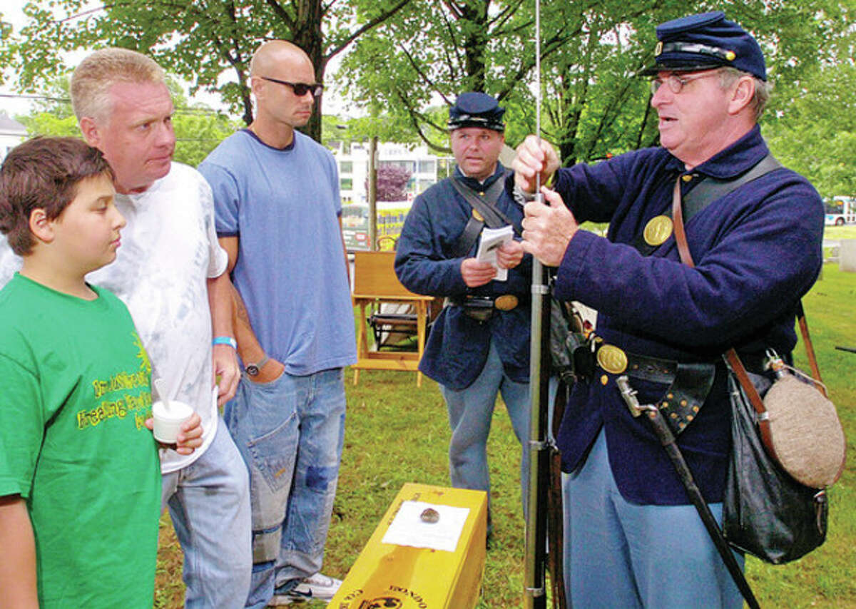Brian Shay of the 11th CT Regiment shows Ernie Rafa ,Ernie Rafa Jr and Jared Civitelli how to load a musket at the Taste of History: Civil War fundraiser Saturday at Mill Hill Historic Park. Hour photo / Erik Trautmann