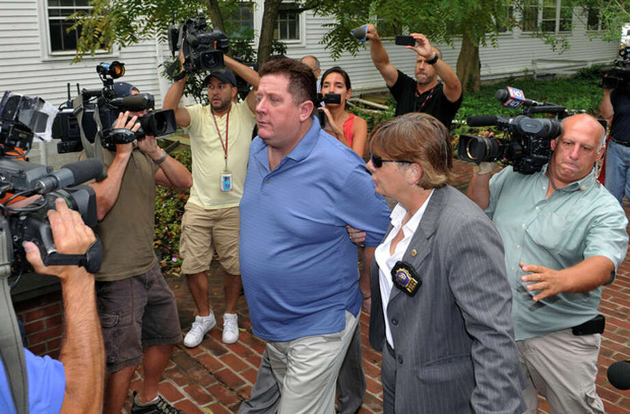 Raymond Roth, center, is escorted by law enforcement officers to the Long Island State Park Police Headquarters, Wednesday, Aug. 15, 2012 in Babylon, N.Y. Roth is suspected of faking his own drowning at a New York beach in a scheme to collect on a life insurance policy. The 47-year-old was reported missing by his son on July 28 at Jones Beach. (AP Photo/Kathy Kmonicek) / FR170189 AP