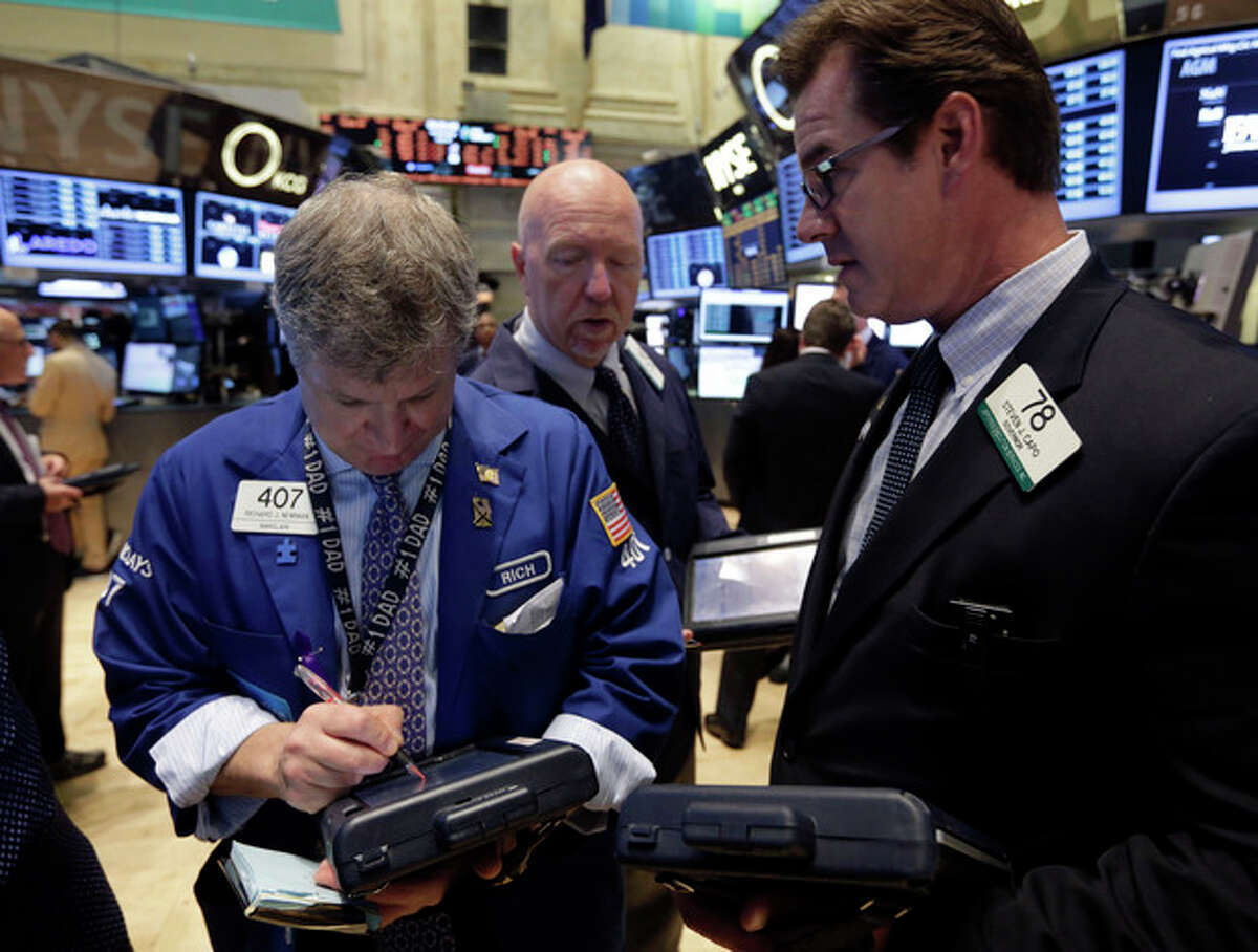 Traders Richard Newman, left, and Steven Capo, right, work on the floor of the New York Stock Exchange Wednesday, July 10, 2013. Stocks nudged higher in early trading Wednesday before the Federal Reserve releases minutes from its most recent meeting. (AP Photo/Richard Drew)