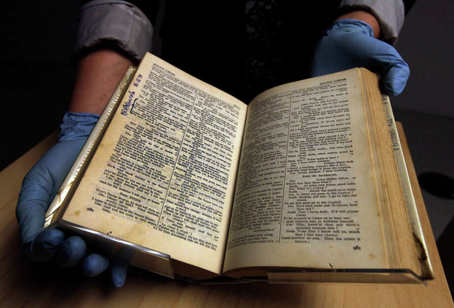 "REMOVES THE LAST SENTENCE OF CAPTION, FILE - In this June 18, 2012 file photo, Becky Allan, project curator of the British Museum, holds an edition of the Complete Works of William Shakespeare, which was kept at South Africa's apartheid-era Robben Island jail in the 1970's, during a photo call ahead of an upcoming exhibition at the museum, central London. The book, which was kept by political prisoner Sonny Venkatrathnam, is signed by 33 inmates - including former South African leader Nelson Mandela. In 1977, he signed his name beside a passage from ""Julius Caesar"". The lines are reminiscent of Mandela's electrifying declaration in a 1960's courtroom that he was prepared to die for his beliefs; today they carry added poignancy as the 94-year-old former president lies gravely ill in a hospital. (AP Photo/Lefteris Pitarakis) / AP"