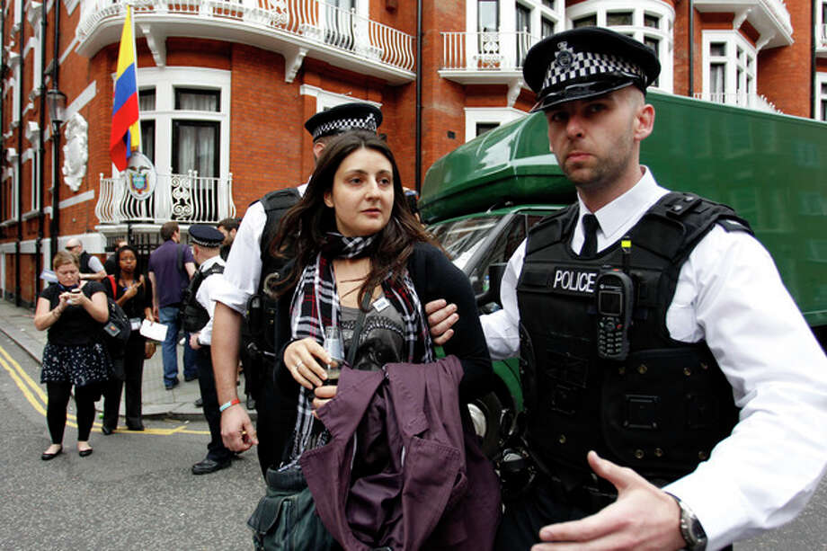 British police officers move a protester in support of WikiLeaks founder Julian Assange from the front of Ecuadorian Embassy in central London, London, Thursday, Aug. 16, 2012. WikiLeaks founder Julian Assange entered the embassy in June in an attempt to gain political asylum to prevent him from being extradited to Sweden, where he faces allegations of sex crimes, which he denies. (AP Photo/Sang Tan) / AP