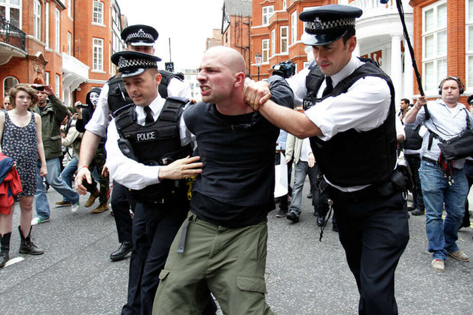 British police officers arrest a protesters in support of WikiLeaks founder Julian Assange from the front of Ecuadorian Embassy in central London, London, Thursday, Aug. 16, 2012. WikiLeaks founder Julian Assange entered the embassy in June in an attempt to gain political asylum to prevent him from being extradited to Sweden, where he faces allegations of sex crimes, which he denies. (AP Photo/Sang Tan) / AP