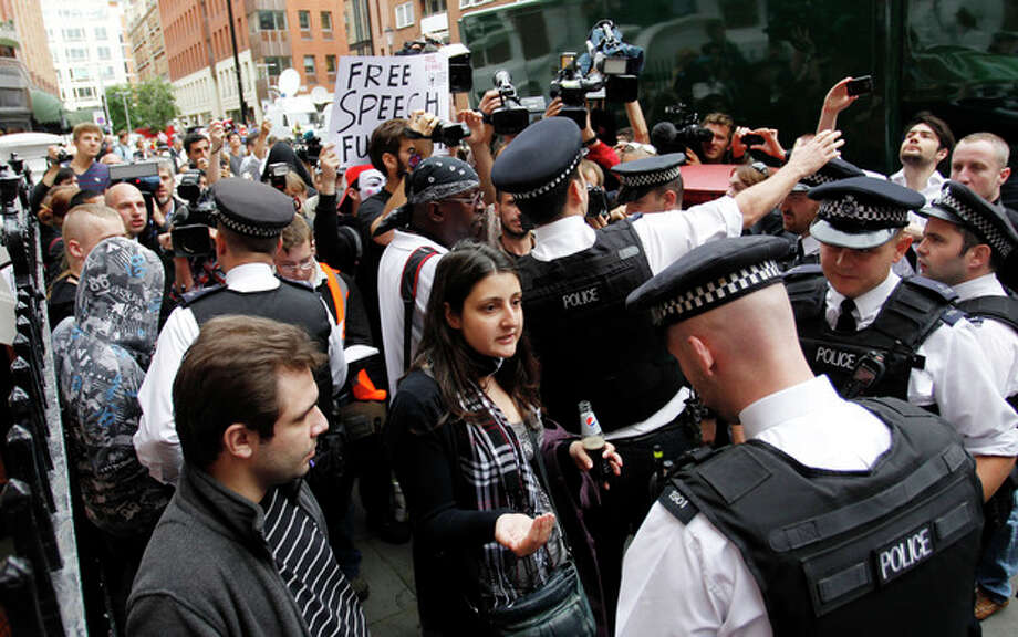 British police officers move the protesters in support of WikiLeaks founder Julian Assange from the front of the Ecuadorian Embassy in central London, London, Thursday, Aug. 16, 2012. WikiLeaks founder Julian Assange entered the embassy in June in an attempt to gain political asylum to prevent him from being extradited to Sweden, where he faces allegations of sex crimes, which he denies. (AP Photo/Sang Tan) / AP