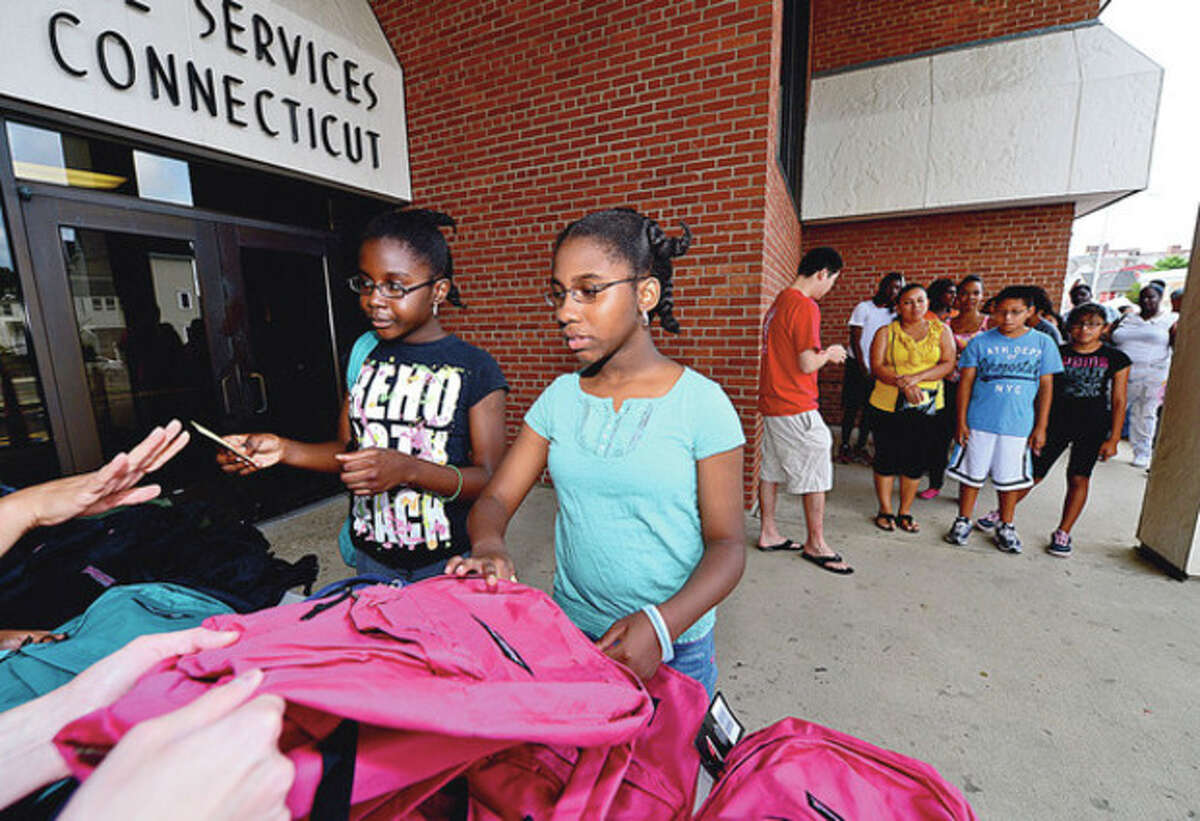 Some 500 Stamford schoolchildren including Amy and Ronalyssa Julien get school supplies and backpacks Saturday at the Stamford police station during the annual event sponsored by the Salvation Army and the Stamford Police Association. Hour photo / Erik Trautmann