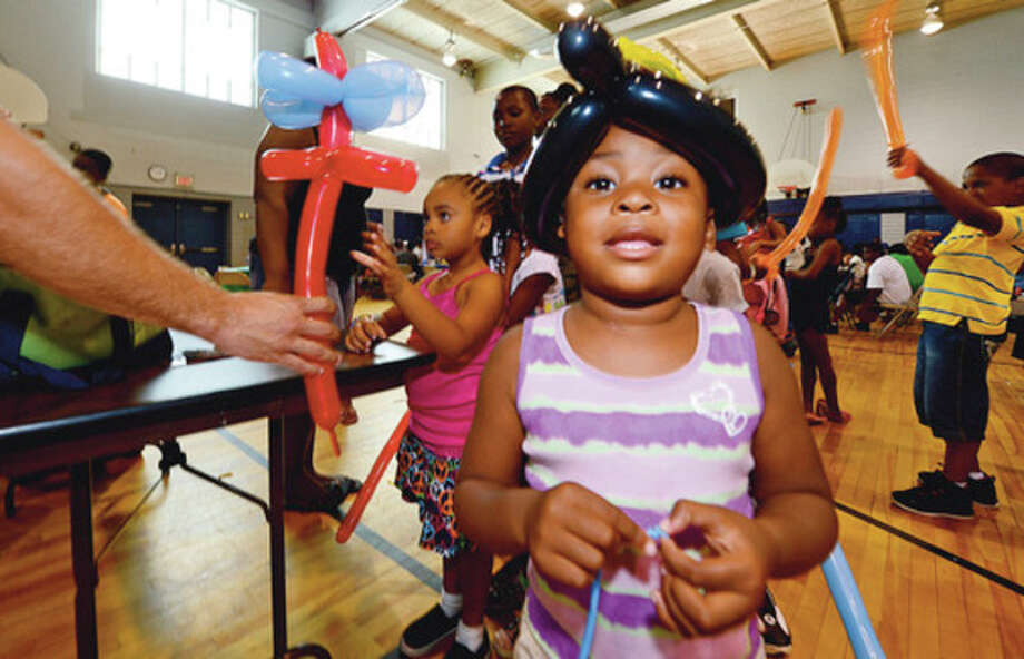 Clockwise, Zariah Smith gets a balloon hat from Magical Memories during the Roodner Court Family Day Saturday at Nathaniel Ely School. Redly Wolfe and Ramonce Charles gets free back packs from the New Beginnings Church. Tamariah Peterson, 4, gets her face painted. / (C)2012, The Hour Newspapers, all rights reserved