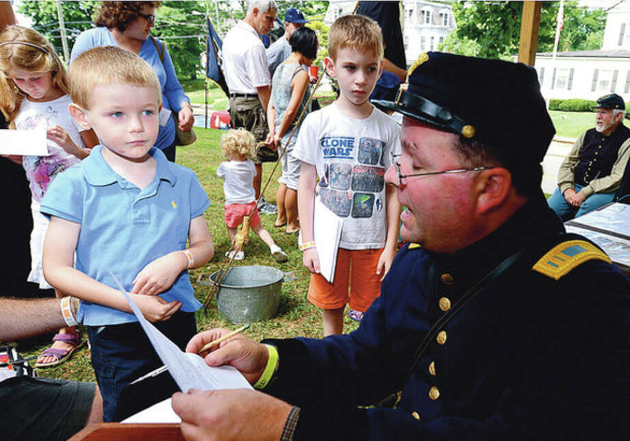Hour photos / Erik TrautmannAbove, Tristan Meyer-Mitchell, 4, enlists into the union army during the Norwalk Historical Society's Civil War BBQ at Mill Hill Historic Park Saturday. Below, Civil War re-enactor Ralph Lim takes a break and enjoys a pulled pork sandwich. / (C)2012, The Hour Newspapers, all rights reserved