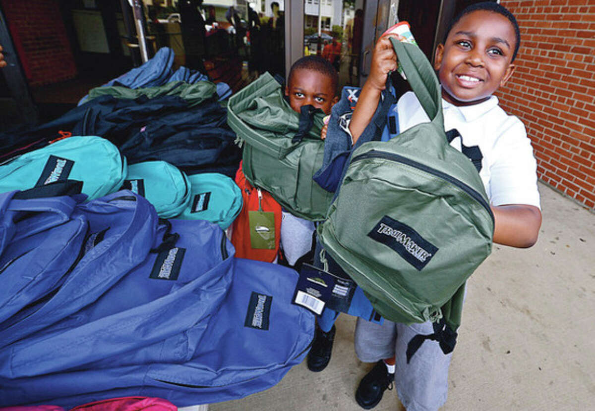 Some 500 Stamford schoolchildren including NaShawn Livingston and his little brother Michael get school supplies and backpacks Saturday at the Stamford police station during the annual event sponsored by the Salvation Army and the Stamford Police Association. Hour photo / Erik Trautmann
