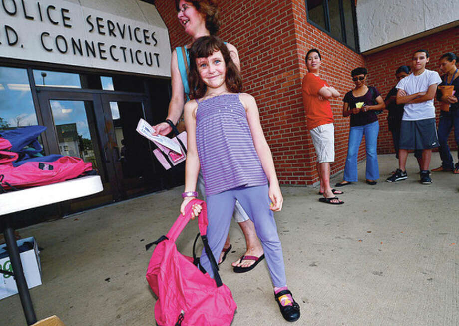 Some 500 Stamford schoolchildren including Kaitlyn Smith, 6, get school supplies and backpacks Saturday at the Stamford police station during the annual event sponsored by the Salvation Army and the Stamford Police Association.Hour photo / Erik Trautmann / (C)2012, The Hour Newspapers, all rights reserved