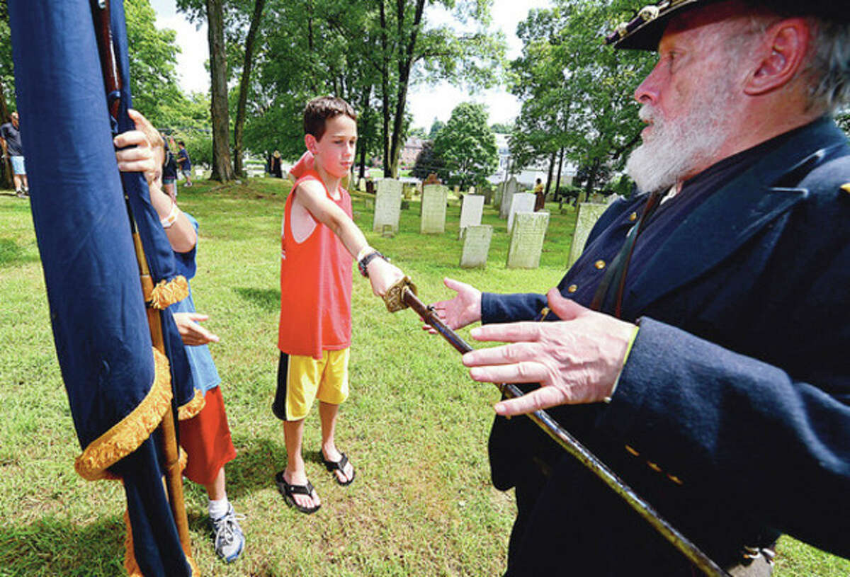 13 year old Josh Tilton tries to draw a civil war era sword during the Norwalk Historical Society's Civil War BBQ at Mill Hill Historic Park Saturday. Hour photo / Erik Trautmann