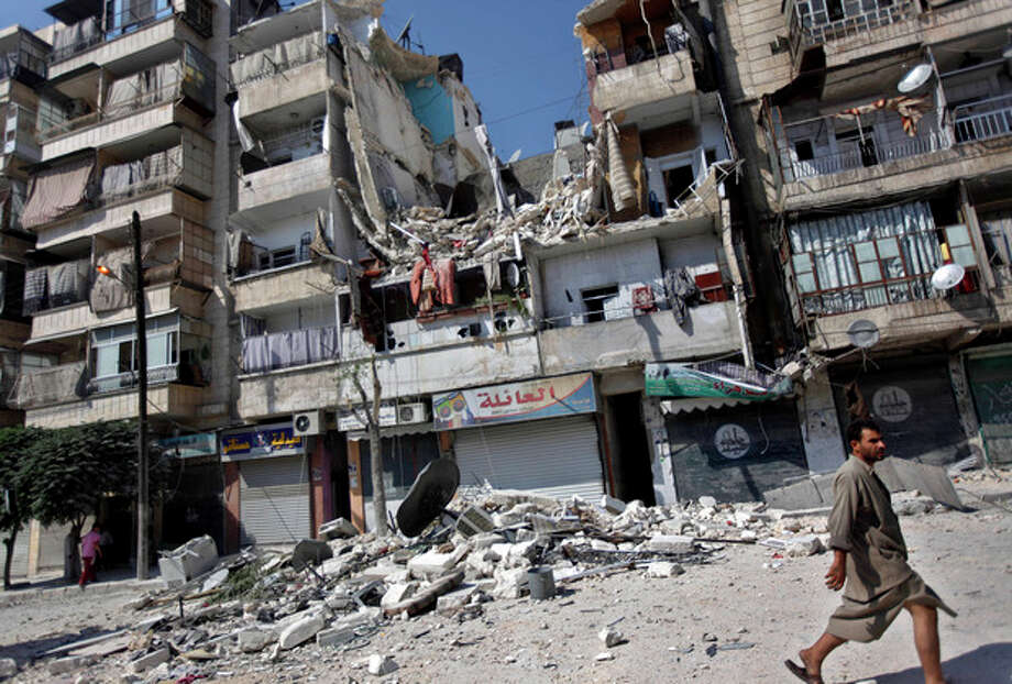 A Syrian man walks by a building destroyed in an airstrike in Aleppo city, Syria, Friday, Aug. 17, 2012. Rebel footholds in Aleppo have been the target of weeks of Syrian shelling and air attacks as part of wider offensives by President Bashar Assad's regime. Rebels have been driven from some areas, but the report of clashes near the airport suggests the battles could be shifting to new fronts. (AP Photo/Khalil Hamra) / AP